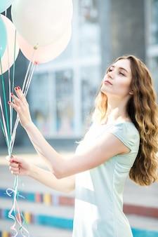 Portret młodej marzycielskiej kobiety z latającymi wielokolorowymi balonami w mieście