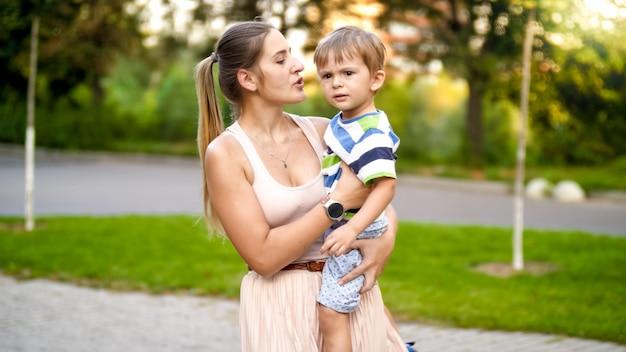 Portret młodej matki przytulającej swojego 3-letniego synka i rozmawiającej z nim podczas spaceru po parku
