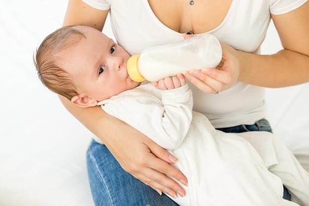 Portret młodej matki trzymającej dziecko i karmiącej mlekiem z butelki