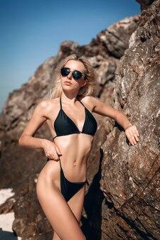 Portret młodej modelki w czarnym bikini i okularach przeciwsłonecznych, pozująca obok skały z ogromnymi kamieniami na tle nieba.