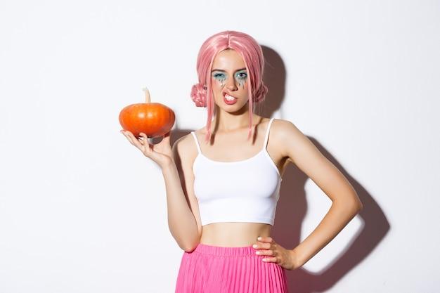 Portret młodej modelki w różowej peruce, trzymającej dynię, świętującej halloween, stojącej na białym tle