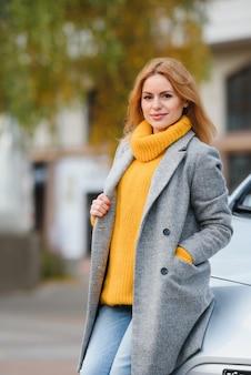 Portret młodej mody piękna kobieta w pobliżu jej samochodu, w mieście. dziewczyna na zakupy.