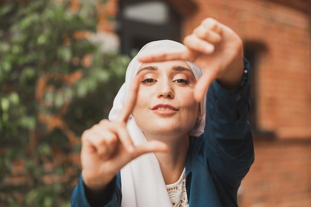 Portret młodej muzułmańskiej dziewczyny, która robi ramkę aparatu palcami na zewnątrz