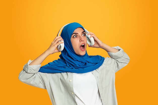 Portret młodej muzułmańskiej kobiety odizolowanej na żółtej ścianie
