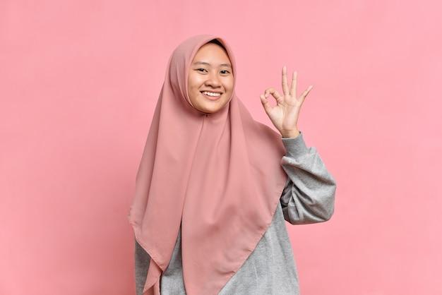 Portret młodej muzułmańskiej kobiety pokazujący znak ok na różowym tle