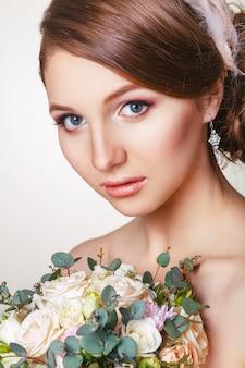 Portret młodej narzeczonej z ornamentem we włosach iz bukietem