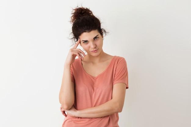 Portret młodej naturalnie wyglądającej uśmiechniętej szczęśliwej hipster ładnej kobiety w różowej koszuli pozowanie na białym tle, myśląc i mając problem