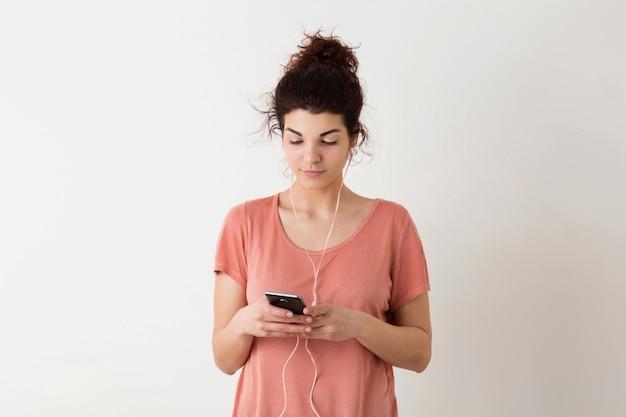 Portret młodej naturalnie wyglądającej uśmiechniętej szczęśliwej kobiety hipster w różowej koszuli pozowanie na białym tle, trzymając inteligentny telefon i słuchanie muzyki w słuchawkach