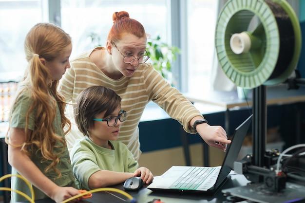 Portret młodej nauczycielki pomagającej dzieciom korzystającym z drukarki 3d podczas zajęć z robotyki i inżynierii w szkole
