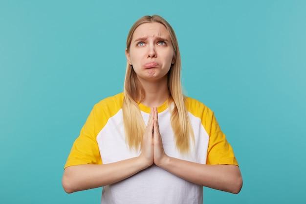Portret młodej nieszczęśliwej jasnowłosej kobiety z długimi włosami ściągającymi usta, patrząc smutno w górę, podnosząc ręce z gestem modlitwy, pozując na niebieskim tle