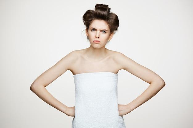 Portret młodej niezadowolonej kobiety w lokówki. kosmetyki kosmetyczne i spa.