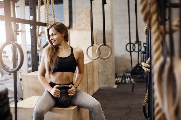 Portret młodej niezwykle dobrze sprawnej kobiety trzymającej ciężar kettlebell siedzącej na pudełku w środowisku siłowni. sport jest świetny dla twojego ciała i wytrzymałości.