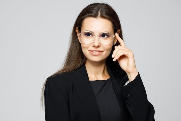 Portret młodej nowoczesnej kobiety biznesu w klasycznym garniturze i okularach