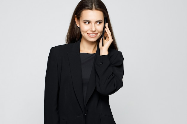 Portret młodej nowoczesnej kobiety biznesu w klasycznym garniturze, rozmawiając na smartfonie