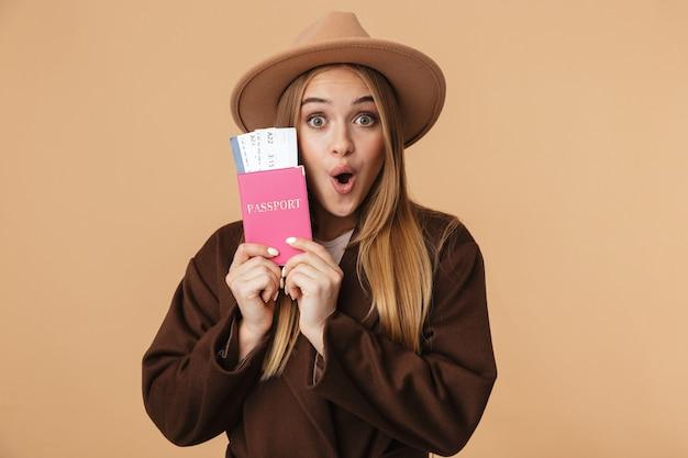 Portret młodej optymistycznej dziewczyny w kapeluszu, trzymającej paszport i bilety podróżne na beżowym tle