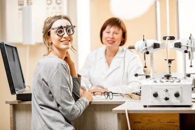 Portret młodej pacjentki ze starszym okulistą podczas konsultacji w gabinecie