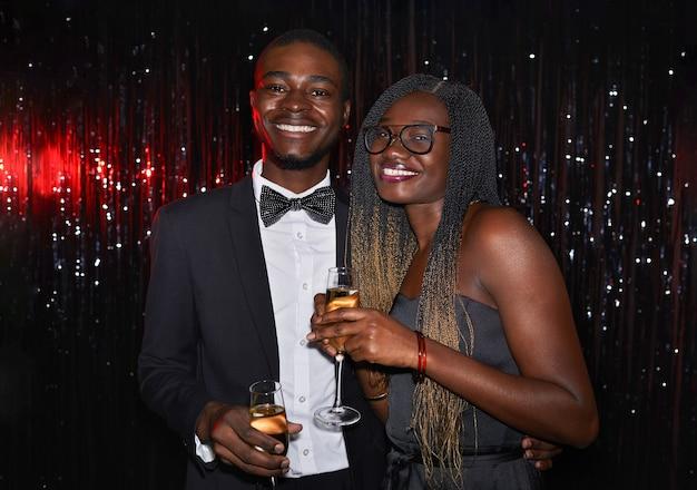Portret młodej pary afroamerykańskiej w pasie trzymającej kieliszki do szampana i uśmiechającej się do kamery, pozując na błyszczącym tle na imprezie, strzał z lampą błyskową