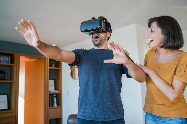 Portret młodej pary bawiącej się razem i grającej w gry wideo w okularach vr podczas pobytu w domu