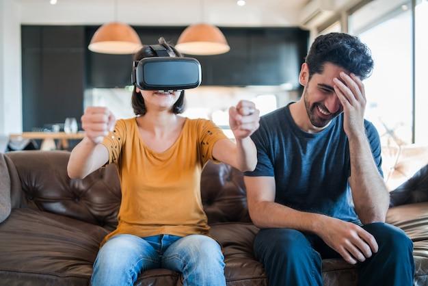 Portret młodej pary bawiącej się razem i grającej w gry wideo w okularach vr, siedząc na kanapie w domu