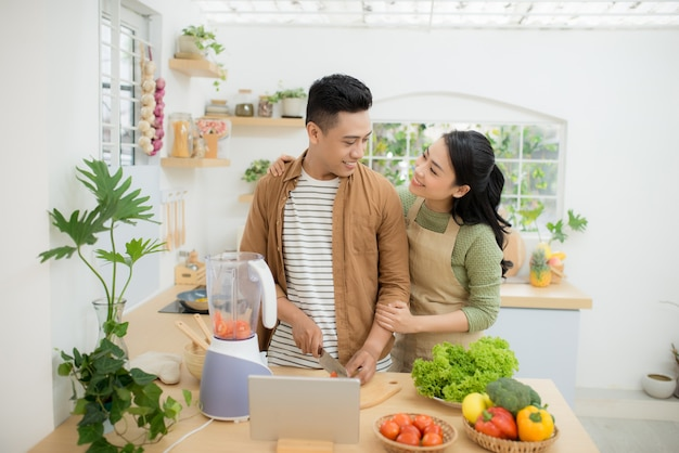 Portret młodej pary, która wspólnie gotuje według przepisu na tablecie