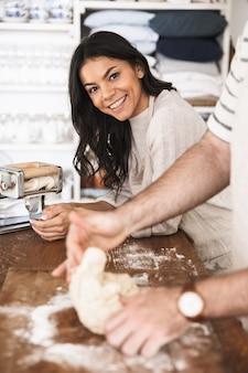 Portret młodej pary mężczyzny i kobiety w wieku 30 lat w fartuchach mieszania ciasta podczas wspólnego gotowania w kuchni w domu