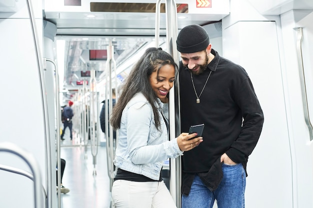 Portret młodej pary międzyrasowej przy użyciu telefonu komórkowego w wagonie metra