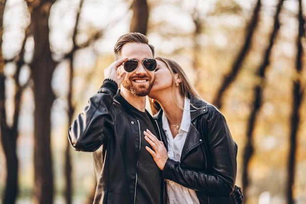 Portret młodej pary miłości. kobieta całuje i przytula swojego mężczyzny w tle parku jesień. historia miłosna