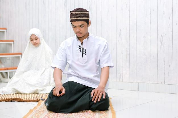 Portret młodej pary muzułmańskich salat razem na macie modlitewnej z ostatnim tahiyat pozowanie