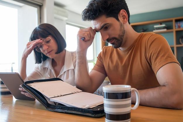 Portret młodej pary obliczania i płacenia rachunków na cyfrowym tablecie z domu. para planująca miesięczny budżet.