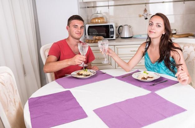 Portret młodej pary opiekającej tosty szklankami wody przed wspólnym jedzeniem domowego posiłku przy stole w małej kuchni