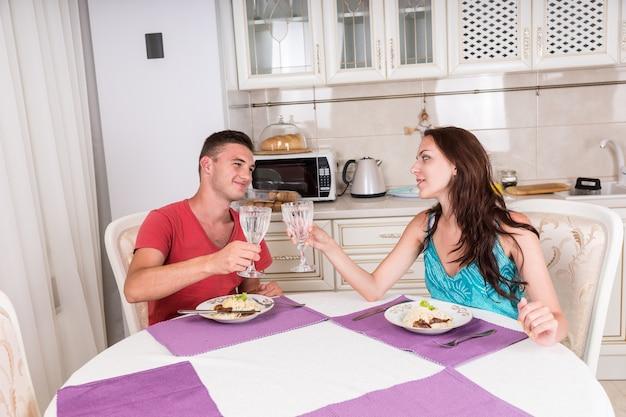 Portret młodej pary opiekania szklankami wody i wpatrywania się w siebie przed wspólnym jedzeniem domowego posiłku przy stole w małej kuchni
