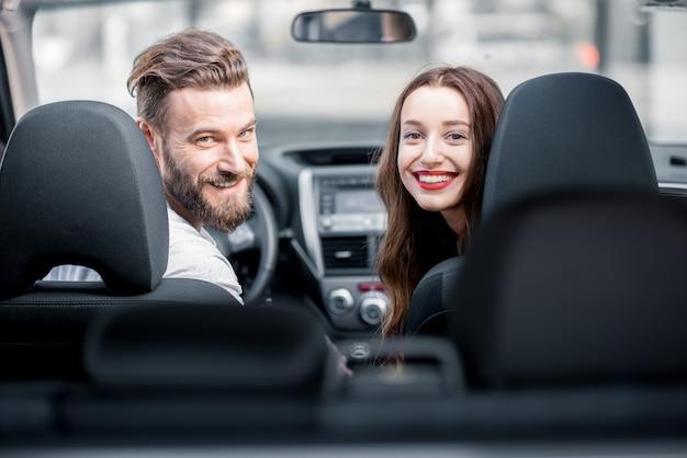 Portret młodej pary patrzącej wstecz, siedzącej na przednich siedzeniach samochodu
