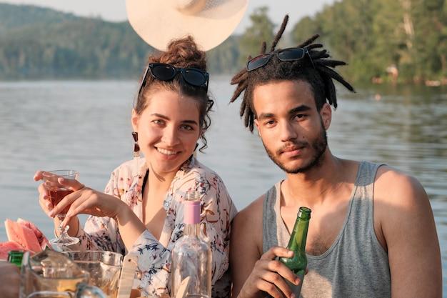 Portret młodej pary picia piwa i uśmiecha się do kamery, siedząc przy stole podczas obiadu na świeżym powietrzu