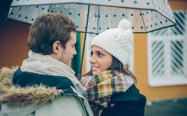 Portret młodej pary piękne patrząc na siebie z miłością pod parasolem w jesienny deszczowy dzień. koncepcja relacji miłości i para.