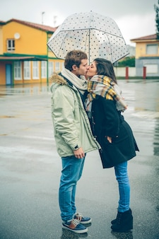Portret młodej pary piękny całowanie pod parasolem w jesienny deszczowy dzień. koncepcja relacji miłości i para.