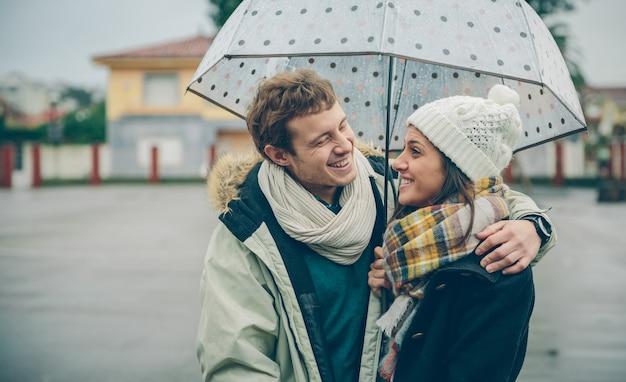 Portret młodej pary piękny obejmując i śmiejąc się pod parasolem w jesienny deszczowy dzień. koncepcja relacji miłości i para.