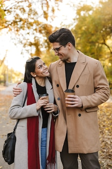 Portret młodej pary pijącej kawę na wynos z papierowych kubków i patrzący na siebie podczas spaceru w jesiennym parku