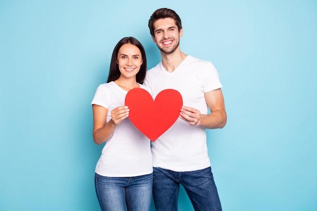 Portret młodej pary pozowanie na ścianie w kolorze niebieskim