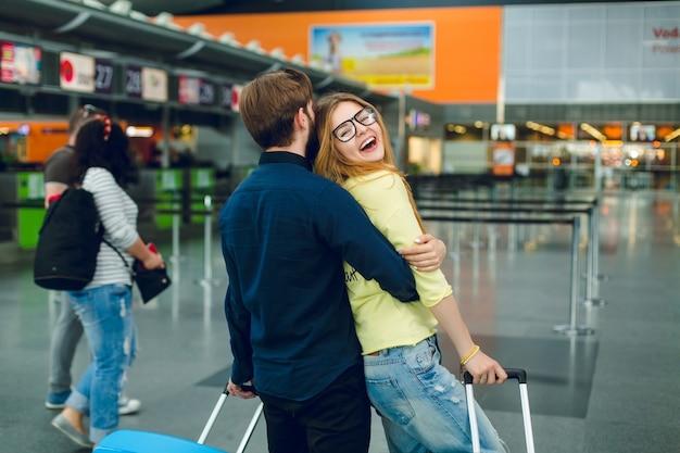 Portret młodej pary przytulanie na lotnisku. ma długie włosy, żółty sweter, dżinsy i uśmiecha się do kamery. w pobliżu ma czarną koszulę, spodnie i walizkę. widok z tyłu.