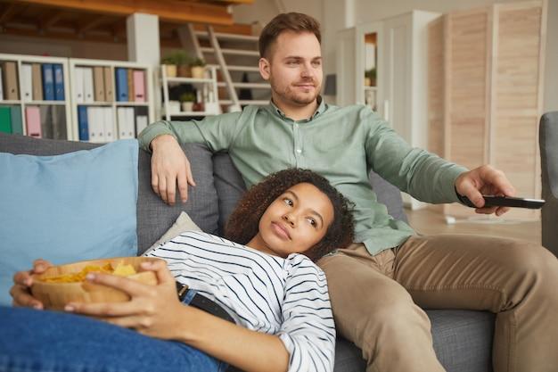 Portret młodej pary rasy mieszanej, oglądając telewizję w domu i jedząc przekąski, relaksując się na wygodnej kanapie