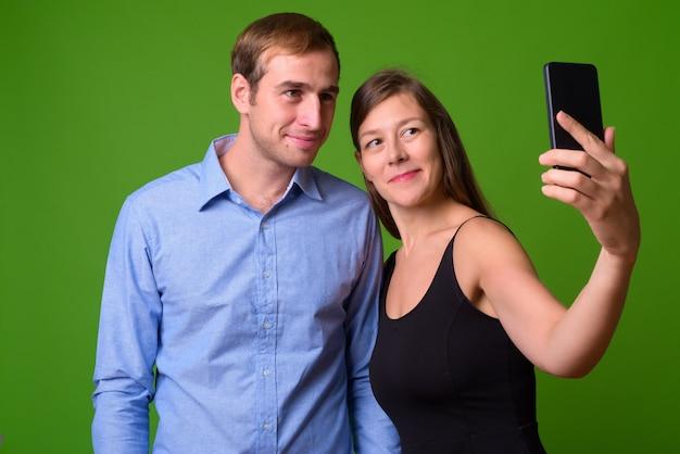 Portret młodej pary razem przed zieloną ścianę