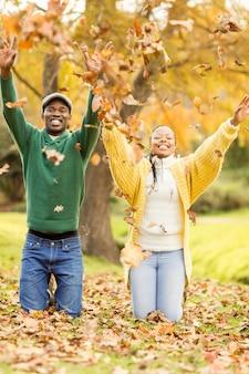 Portret młodej pary rzucania liści wokół