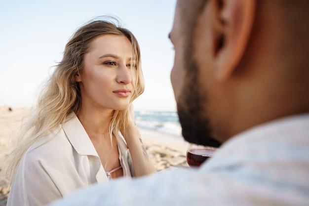 Portret młodej pary siedzącej na plaży i pijącej wino