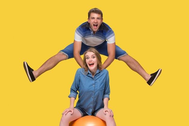 Portret młodej pary skoki na żółtą ścianę