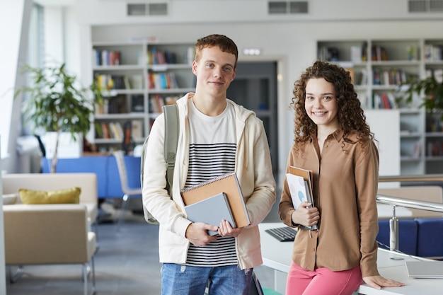 Portret młodej pary studentów w pasie i uśmiechnięty, stojąc w bibliotece uczelni trzymając książki,