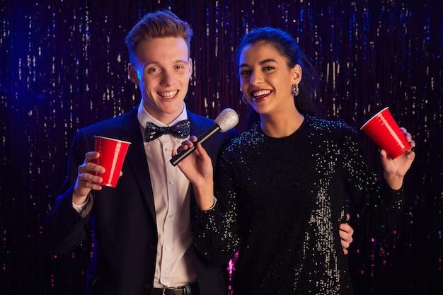 Portret młodej pary trzymając mikrofon i uśmiechając się do kamery, ciesząc się imprezą karaoke