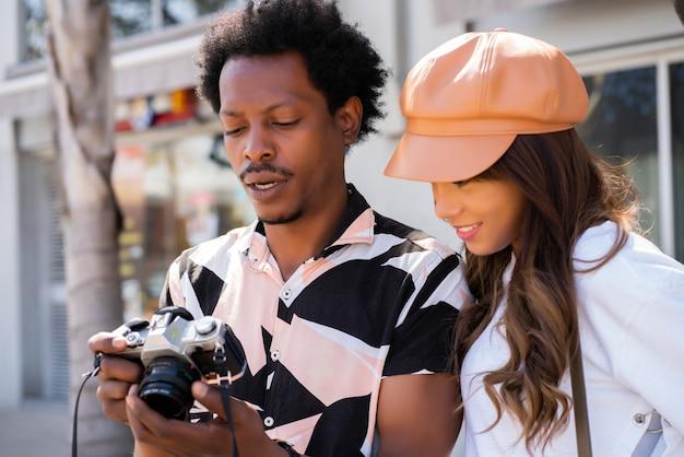 Portret młodej pary turystów korzystających z aparatu i robiących zdjęcia w mieście