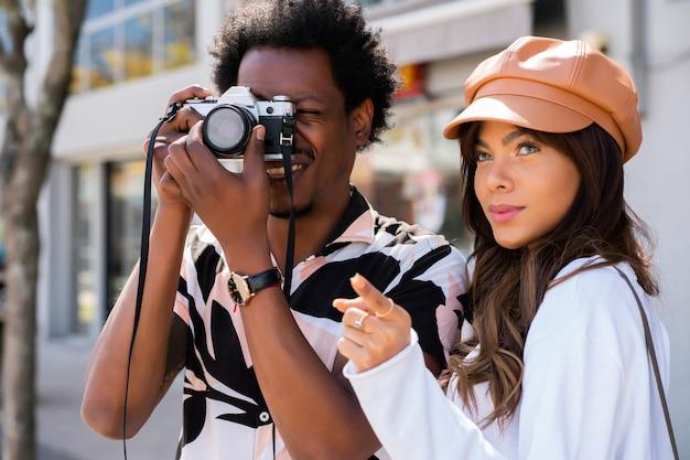 Portret młodej pary turystycznej za pomocą aparatu fotograficznego i robienia zdjęć w mieście