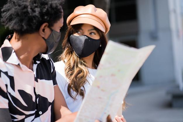 Portret młodej pary turystycznej za pomocą maski ochronnej i patrząc na mapę, szukając wskazówek na zewnątrz