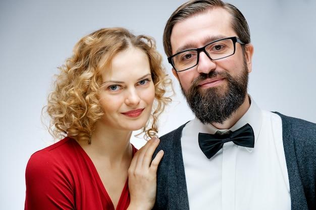 Portret młodej pary w miłości pozowanie studio ubrany w klasyczne ubrania. ścieśniać